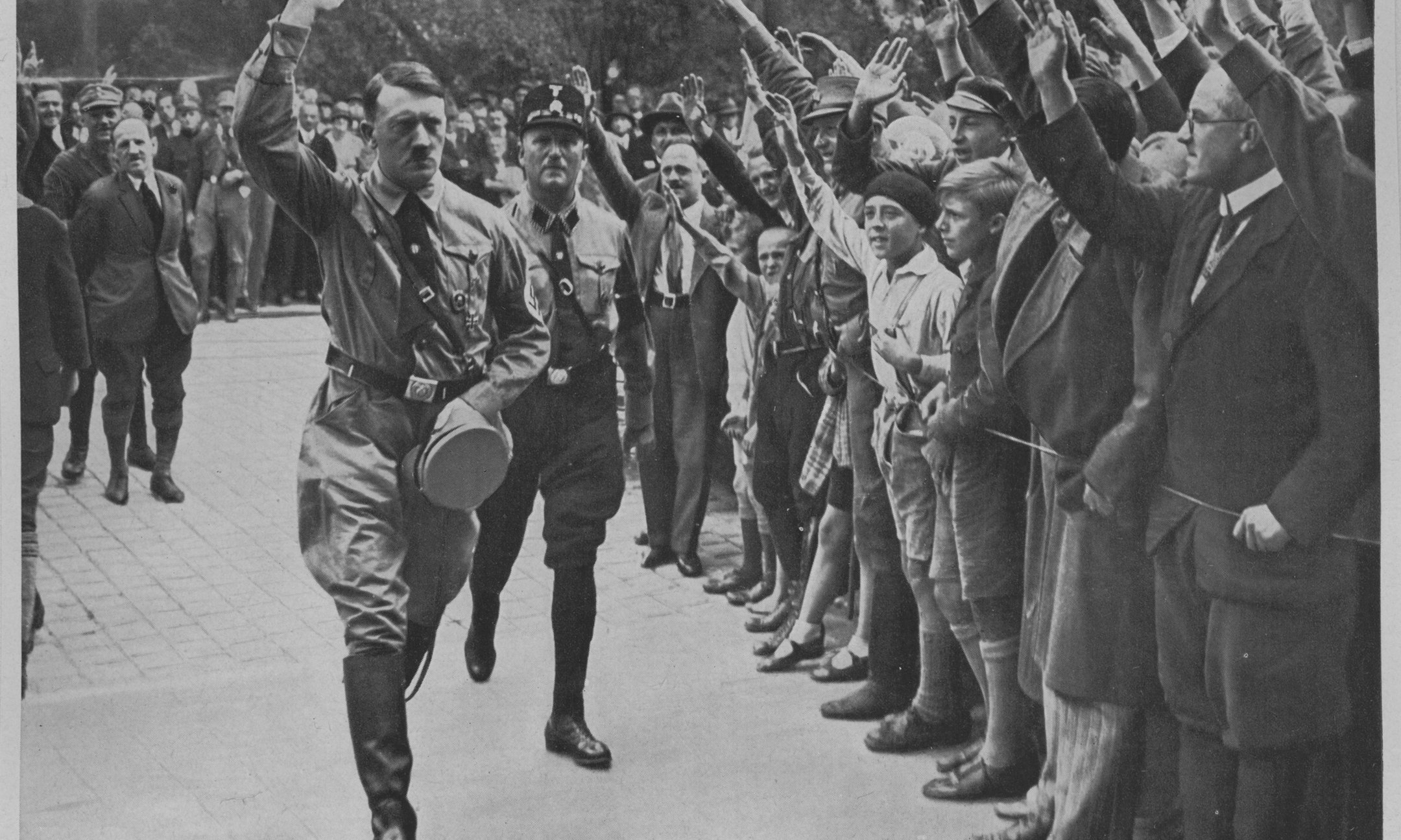 Adolf Hitler's followers greet him at a party conference in Neurenberg (1929). This and other pictures came with packets of cigarettes and were collected in special albums. This picture is from the series Deutschland erwacht [Germany awakes].