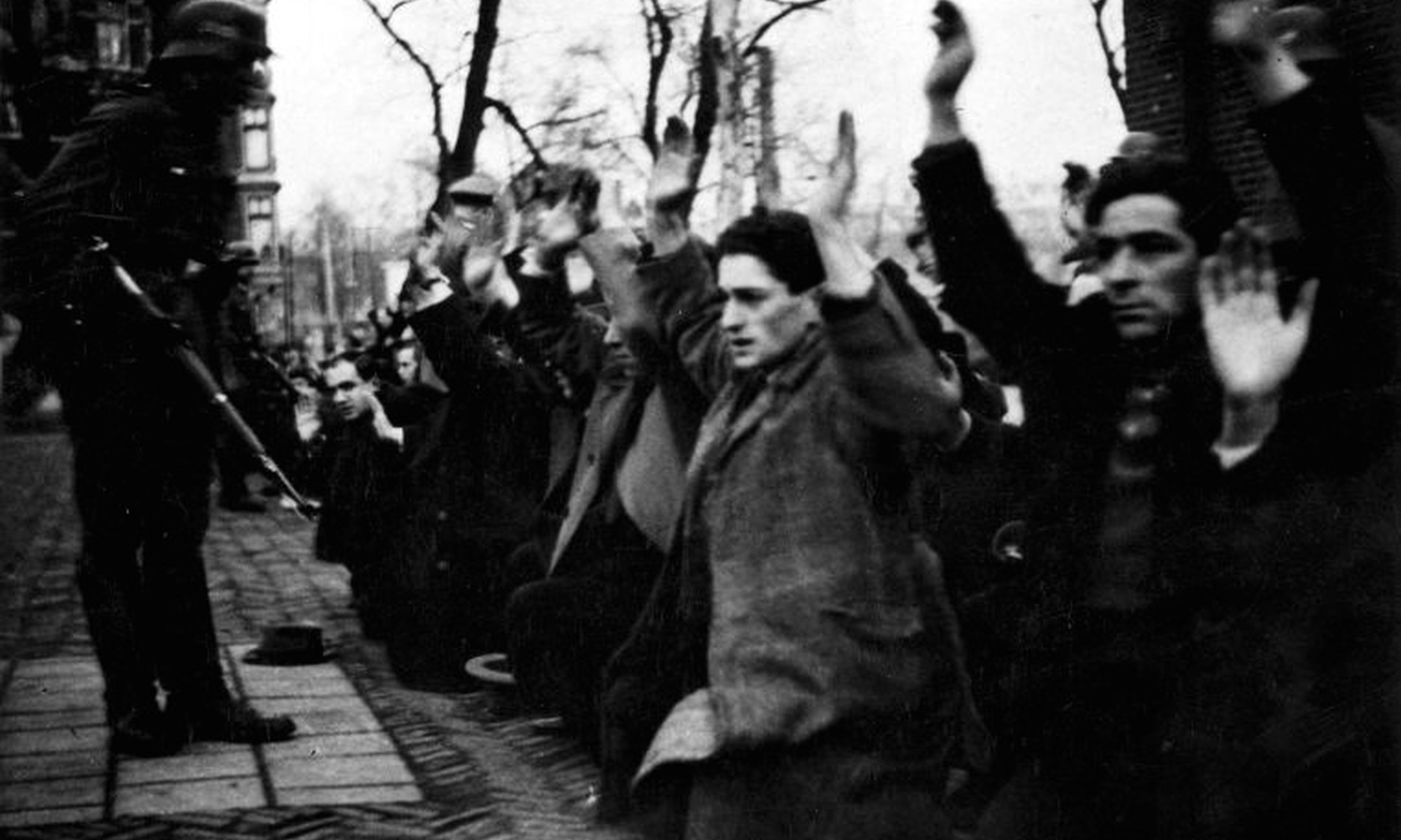 Soldier holds Jews at gunpoint at Jonas Daniël Meijerplein in Amsterdam during one of the first raids in the Netherlands. (22 February 1941).