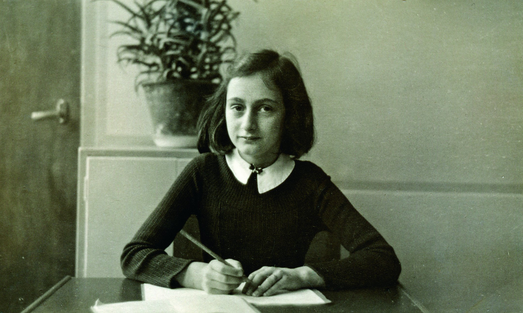 Anne Frank achter haar bureau op de Montessorischool in Amsterdam (winter 1940).  Anne is hier 11 jaar oud en zit in de zesde klas (groep 8).
