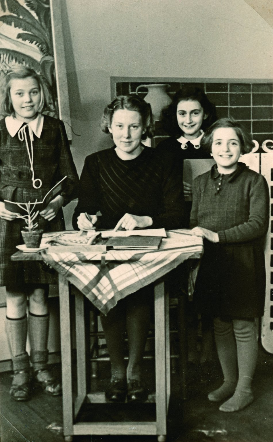 Anne at primary school with her teacher and two classmates. From left to right: Martha van den Berg - Miss Godron - Anne - Rela Salomon.