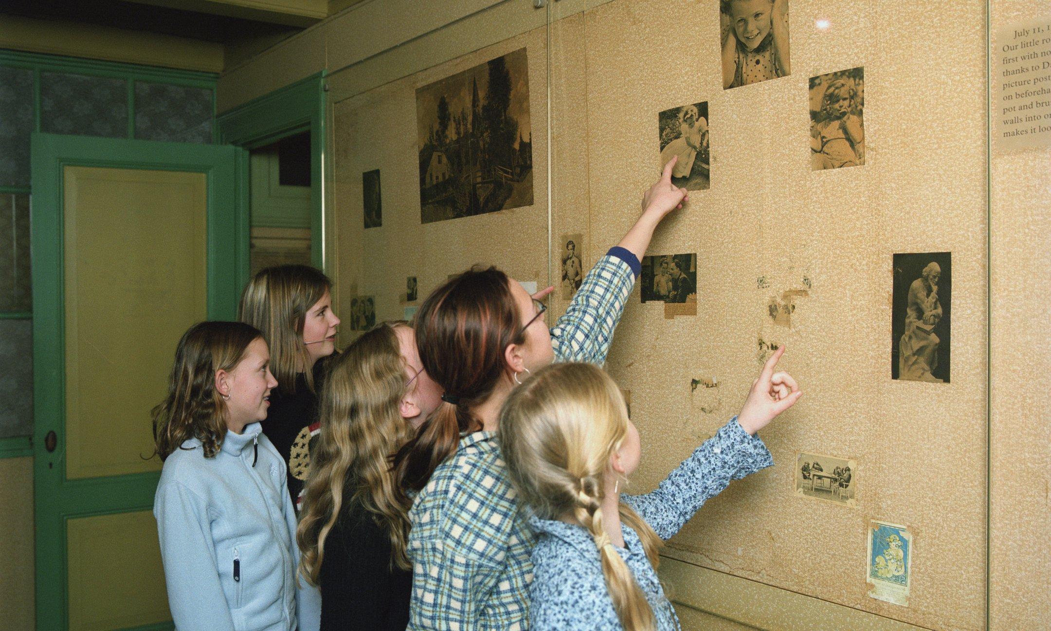 Museumbezoekers bij de plaatjeswand in Annes kamer
