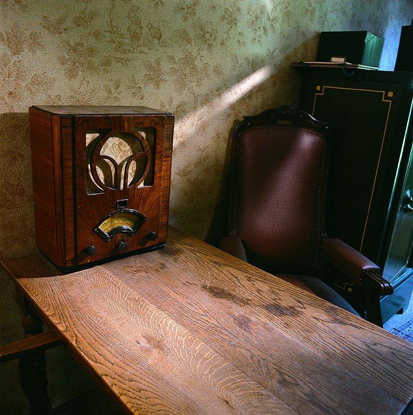 In het privé-kantoor luisteren de onderduikers naar de radio, reconstructie (1999).