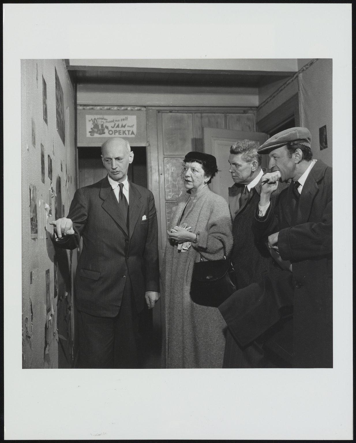 Otto Frank, Frances Goodrich, Albert Hackett en regisseur Garson Kanin in het kamertje van Anne Frank in het Achterhuis. Otto wijst een tekening van Anne aan.