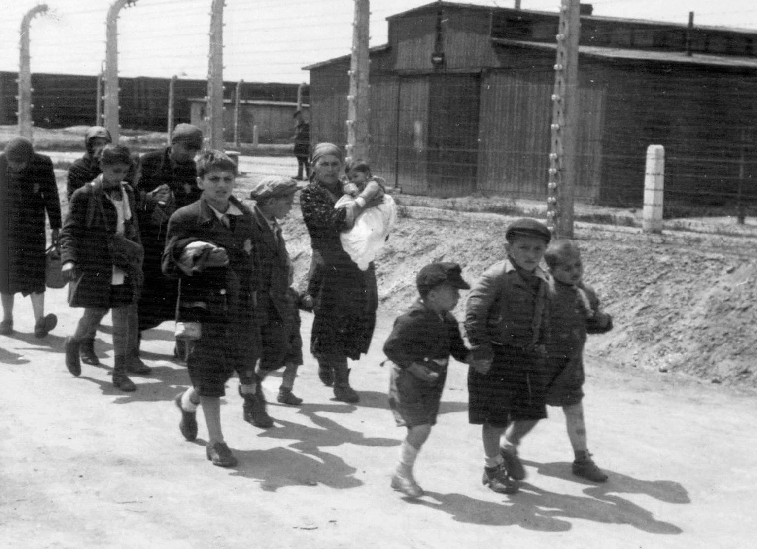 Hungarian women and children are walking to the gas chamber after their arrival at camp Auschwitz-Birkenau. 26 May 1944.