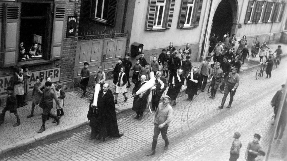 Six Jews are made to walk the streets for hours, wearing prayer shawls and carrying Torah scrolls from the synagogue. They are spit on, scolded, and beaten. The synagogue is looted. Finally, all their belongings are set on fire in the square in front of the town hall.