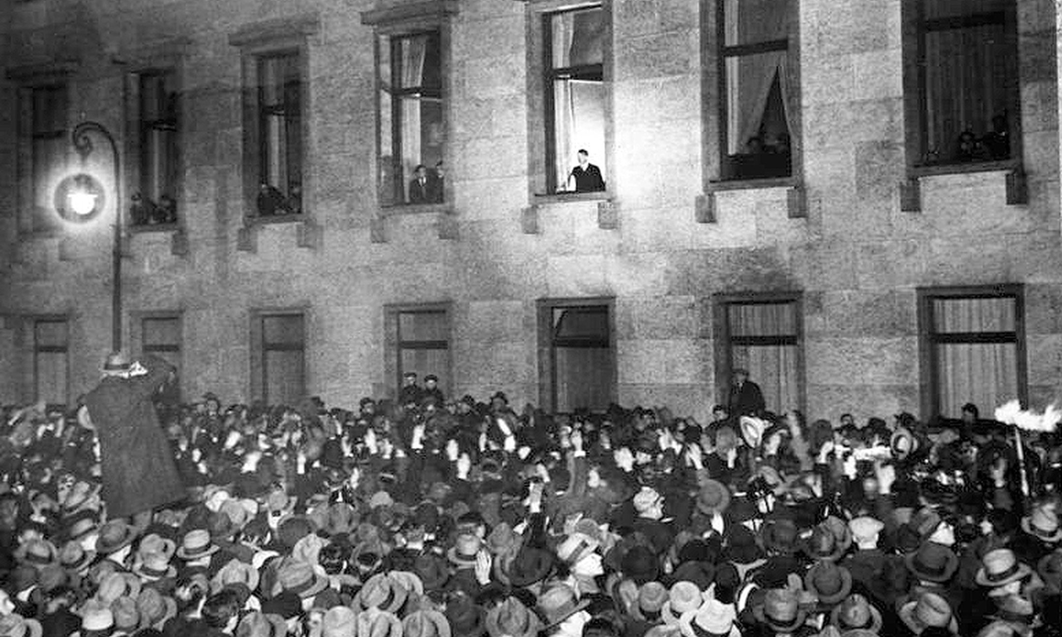 Adolf Hitler waves from the chancellery to the jubilant crowd. They celebrate his appointment as Chancellor of Germany.
