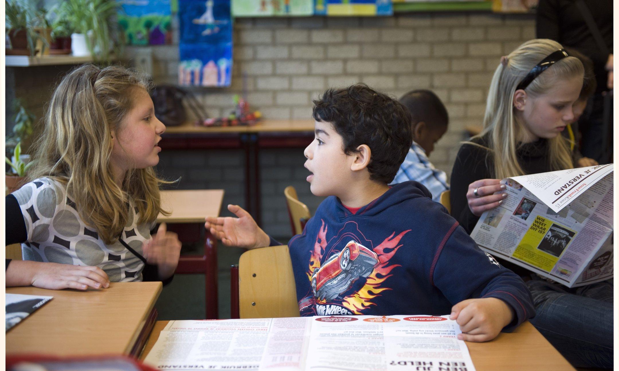 Estudiantes participan activamente en una discusión utilizando el periódico de Ana Frank
